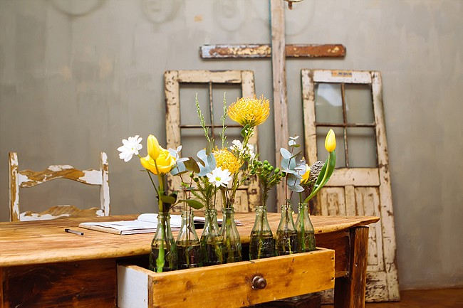 Vintage bottles with single flowers in wooden crate // Yellow and Grey DIY Vintage Wedding // Miracles Photo