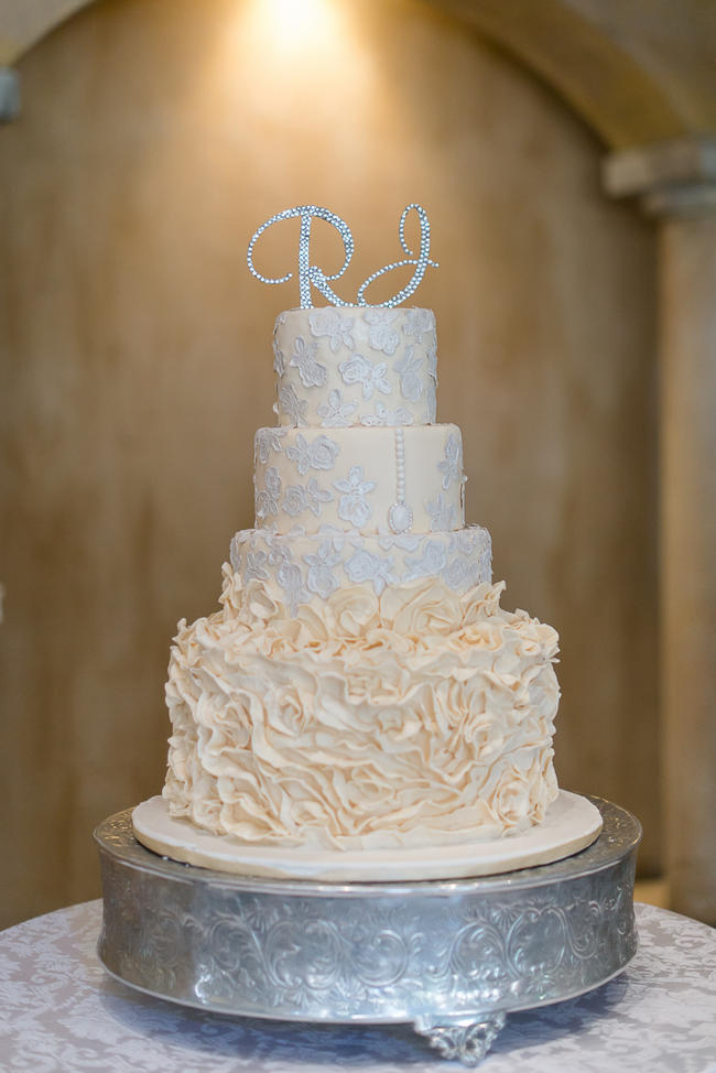 Cream and white ruffled wedding cake with glitter cake topper