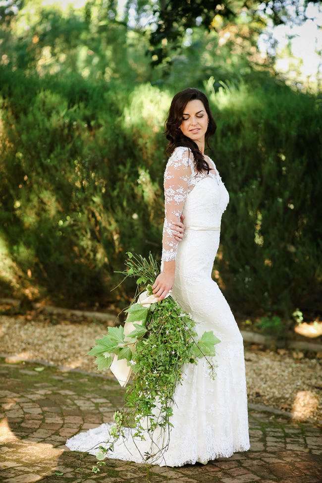 Long, lace sleeved wedding dress with cascade bouquet made of leaves for a Rustic Garden Picnic Wedding // Nikki Meyer Photography