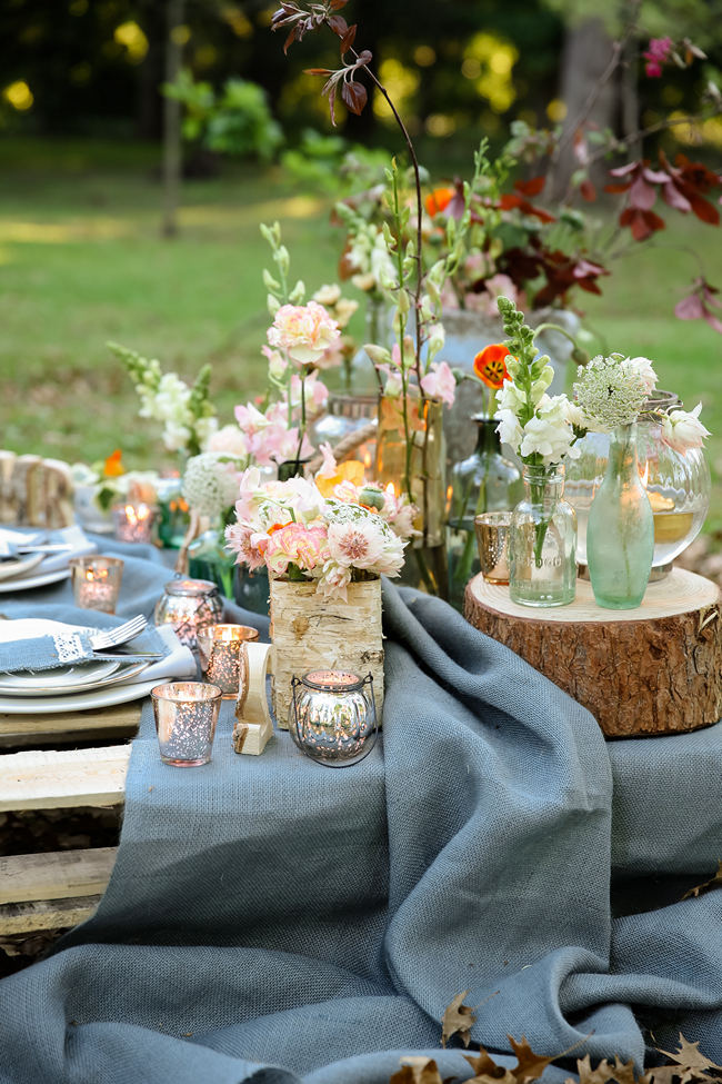 A pretty pallet picnic table using grey hessian burlap runner, filled with rustic decor elements, mercury votives, wood slabs and peach blooms in mix and match vases. Rustic Garden Picnic Wedding // Nikki Meyer Photography