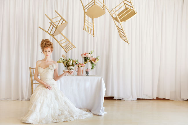 The romantic, ruffled layers of this strapless sweetheart wedding dress and messy bridal upstyle hairdo looking amazing with a backdrop of whimsically floating gold chairs.
