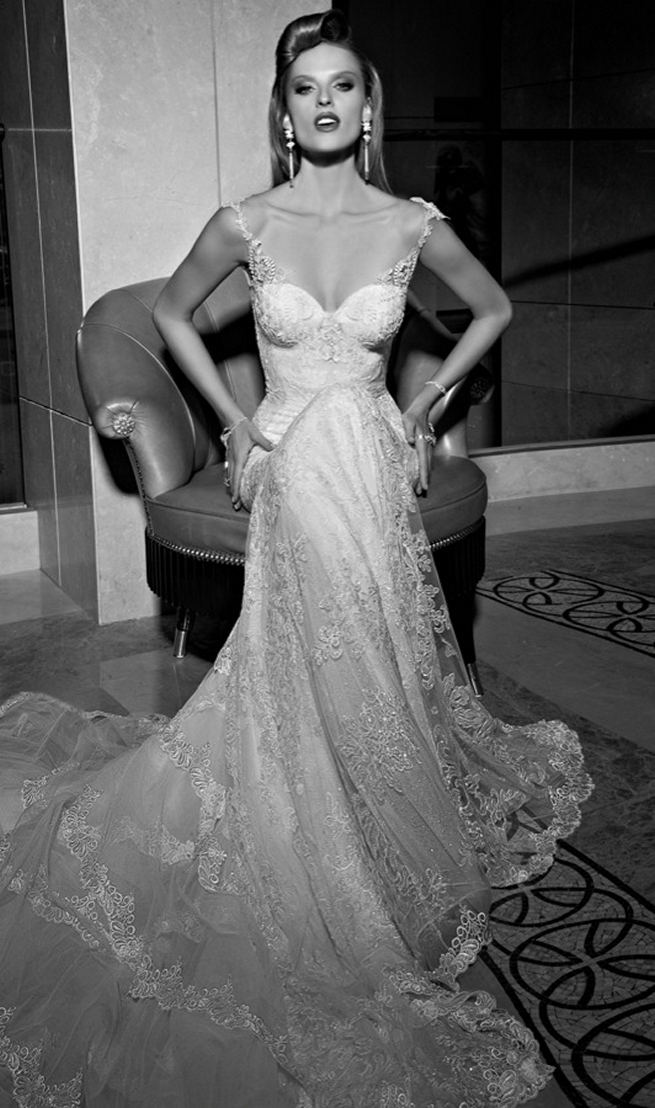Galia Lahav's mermaid style Madison wedding dress has a colossal and dramatic train made from layers and ruffles of tulle and vintage lace. The back falls low with a heart shape. The  sweetheart front is a marriage of two embroidered laces. The sides of the gown are layered with a sheer glittering fabric under an embroidered lace.