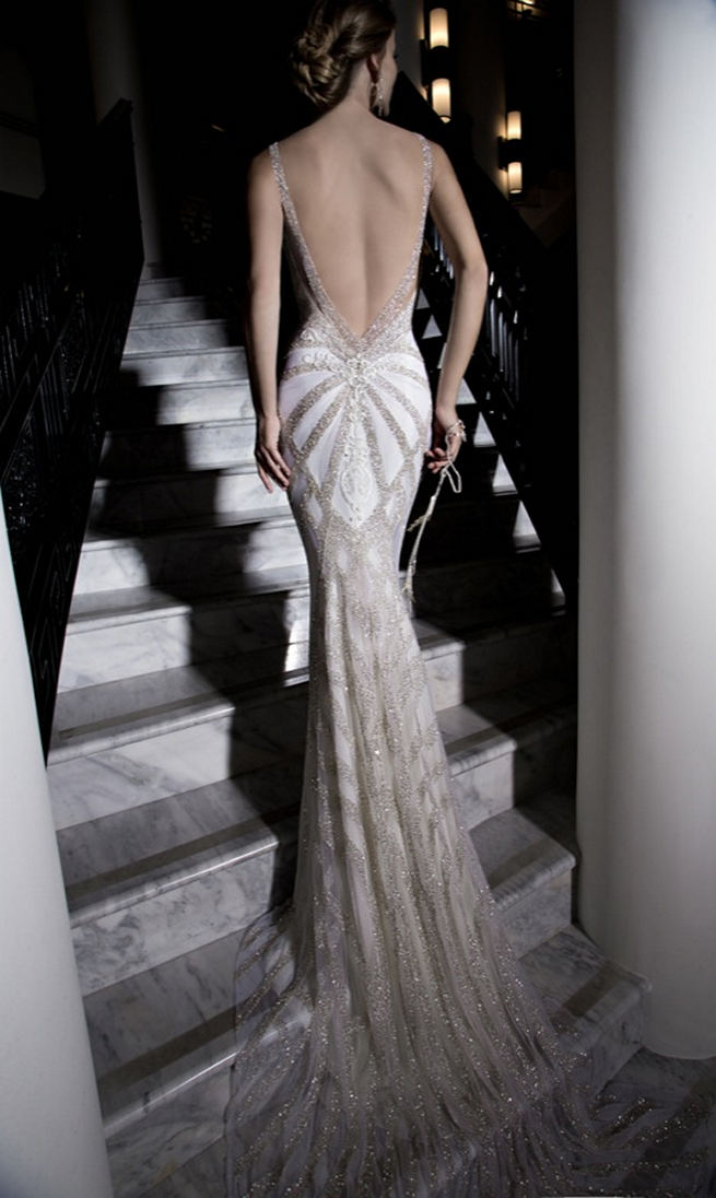 Galia Lahav's backless Katharina Wedding Dress is entirely embroidered in silver glass beads with an art deco geometric pattern. The dress has a front detail of lace paneling and a v-shaped back with graphic ivory lace details.