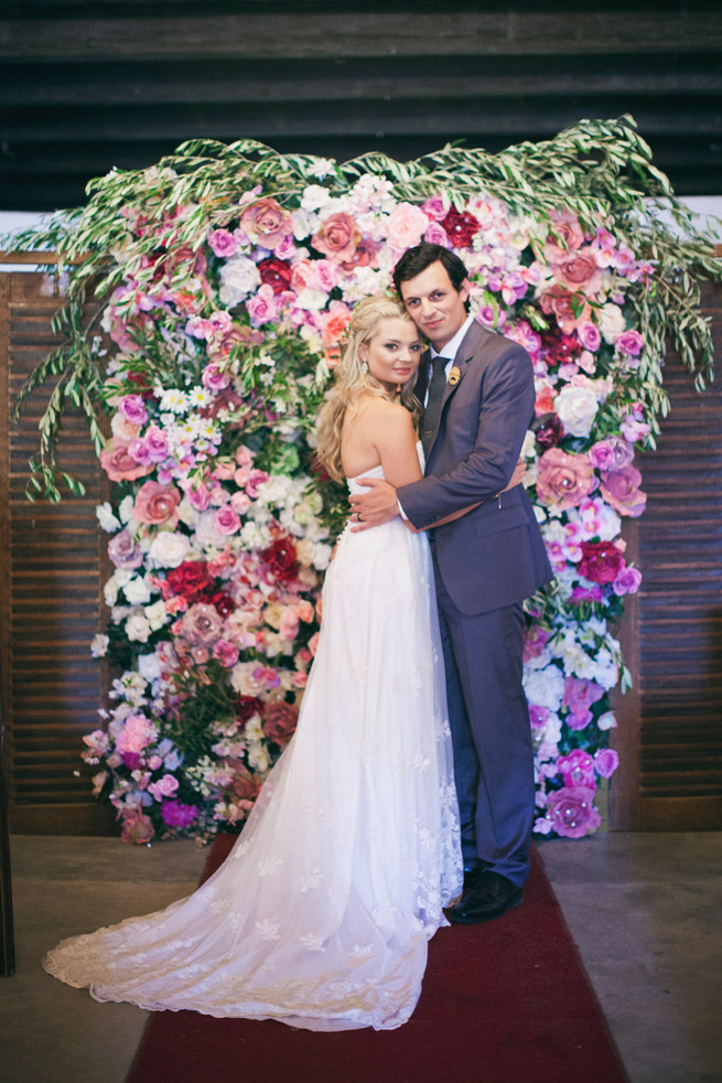 Stunning floral backdrop in pink and red. Groom in grey suit with grey tie. Green White Rustic South African Wedding // Justin Davis Photography