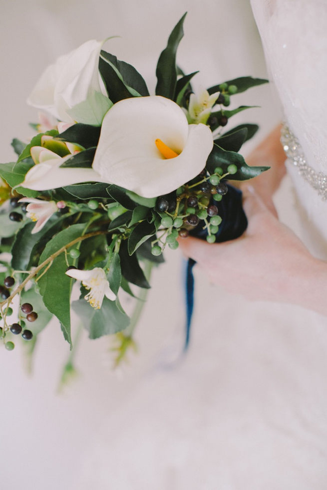 Green and white bridal bouquet with Calla Lily, greens and blue berries wrapped in navy ribbon
