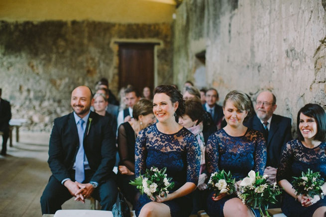 Bridesmaids wearing navy lace sleeved gowns