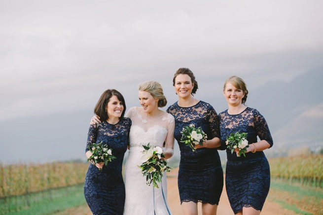 Bridesmaids in short navy dresses with long lace sleeves
