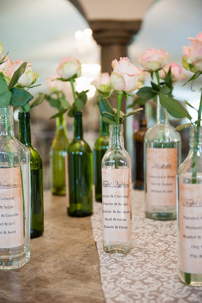 DIY Seating Chart: Vintage bottles holding single stem roses were wrapped in home printed labels and displayed on a table. Blush Pink and Powder Blue Spring Wedding // D'amor Photography