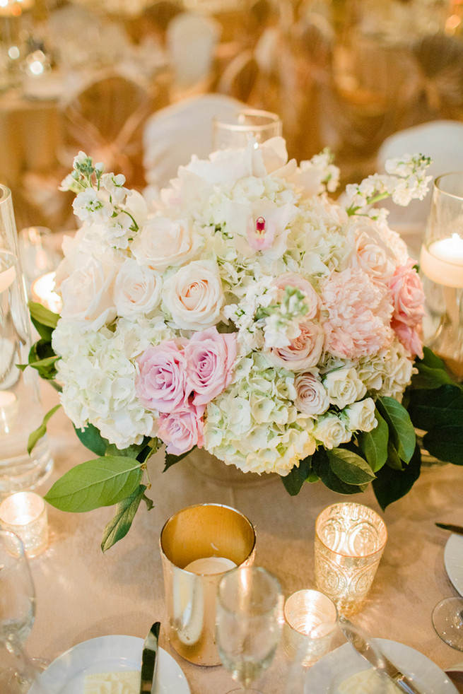 Chic Wedding reception florals of white hydrangea, blush roses, white roses and green fillers with white blossoms.  Clear glass vases with floating candles and silver votives.