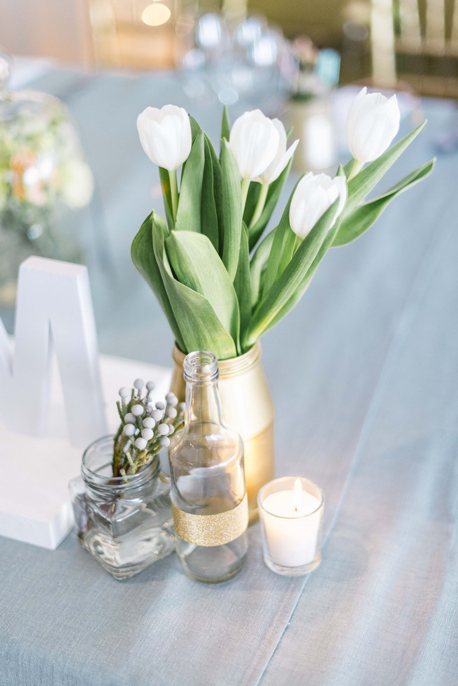 Gold painted bottles on reception tables with white tulips. White and Gold DIY Chevron Wedding, South Africa, by Claire Thomson Photography