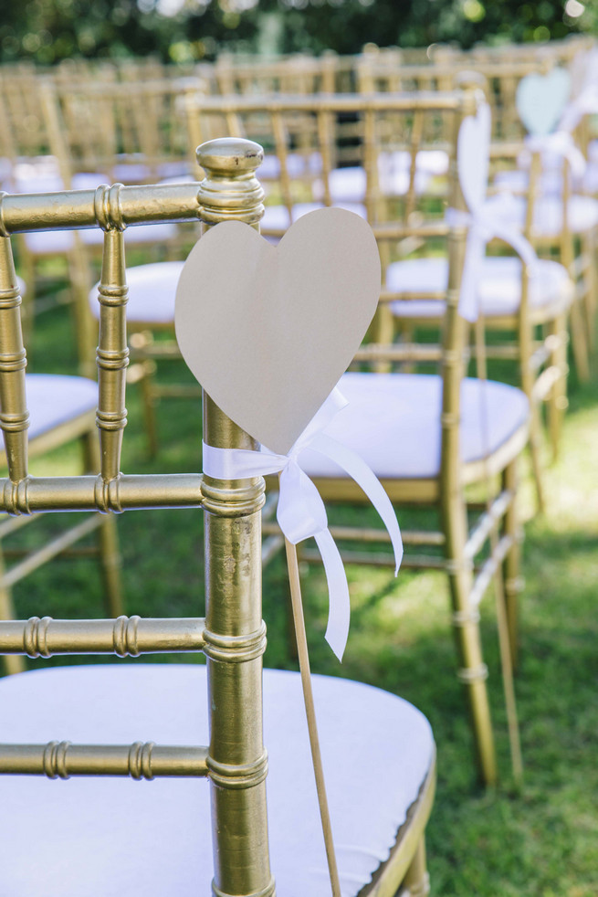 Gold Tiffany chairs with gold DIY hearts. White and Gold DIY Chevron Wedding, South Africa, by Claire Thomson Photography