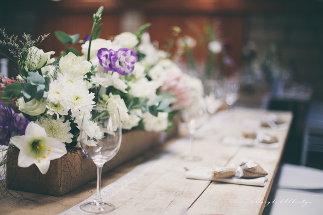 Farm style blooms. Rustic table decor with wood slabs, vintage bottles, lace and single stem roses.