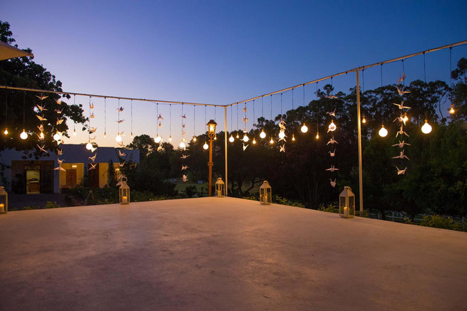 Naked bulbs on outdoor dancefloor / Langkloof Roses Wedding, Cape Town - Claire Thomson Photography