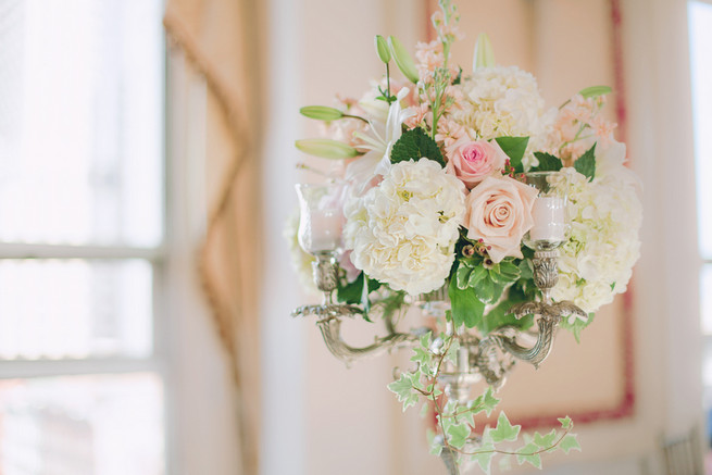 White hydrangea, cream and blush roses, white lillies, ivy wedding floral centerpiece