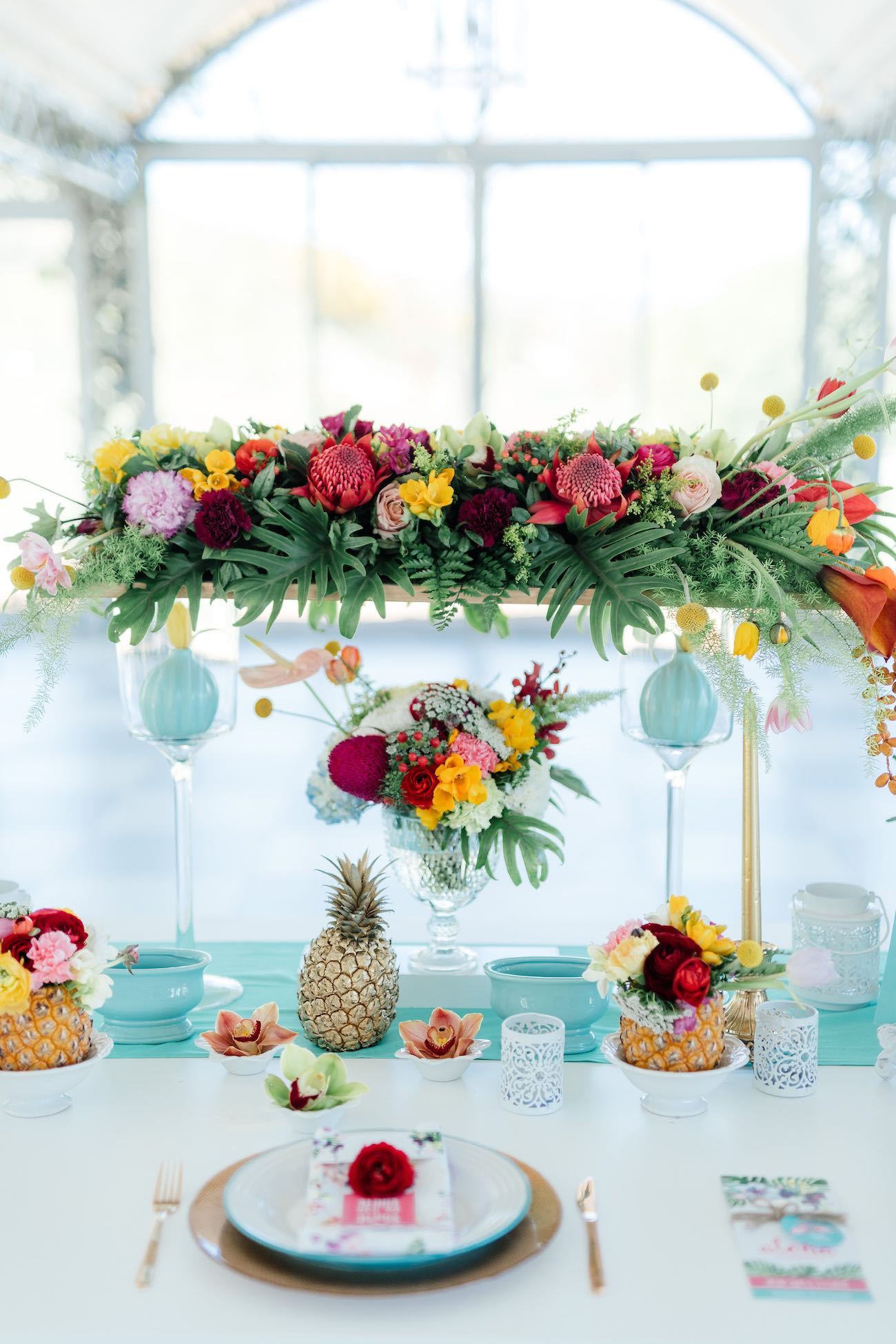 Ridiculously stunning, bright and beautifully tropical tablescape filled with flowers, ferns, pineapples and hand painted details. Click for the most absolutely gorgeous Tropical Wedding ideas ever!